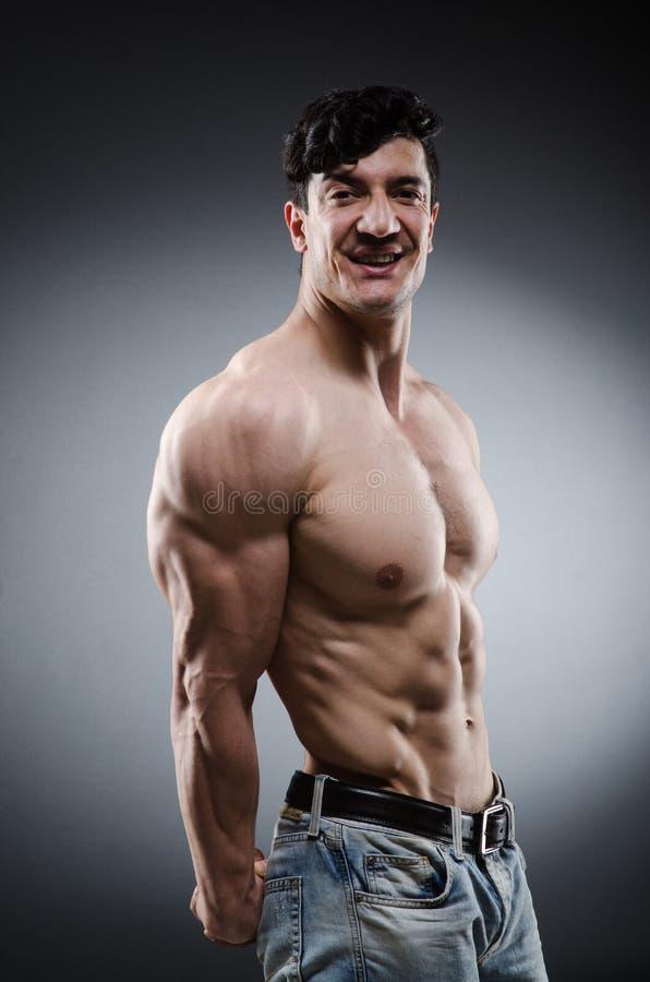 Hombre muscular que presenta en estudio oscuro foto de archivo libre de regalías