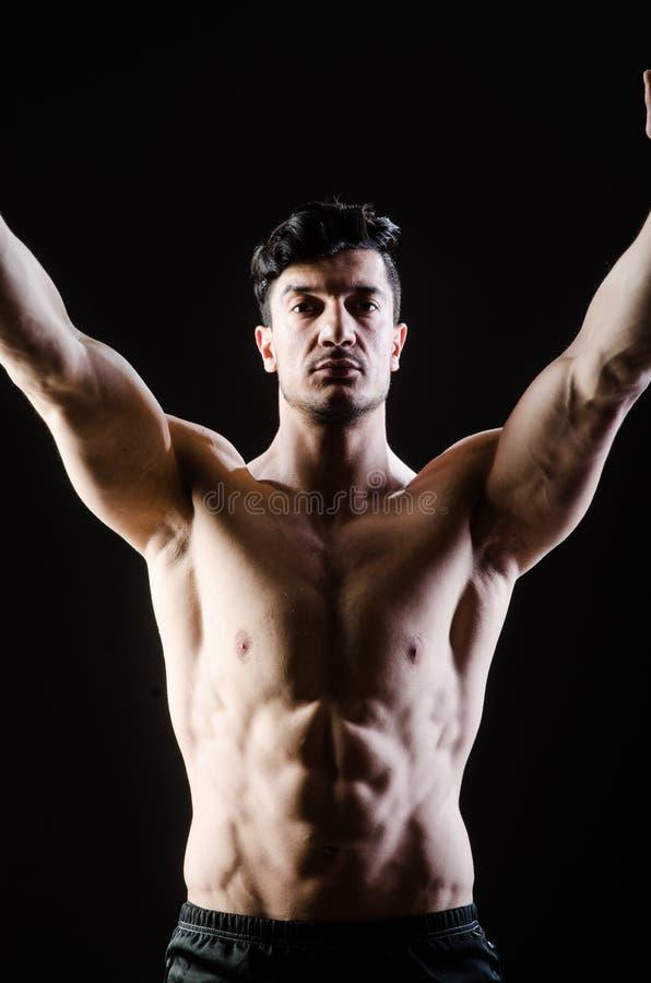 Hombre muscular que presenta en estudio oscuro fotos de archivo libres de regalías
