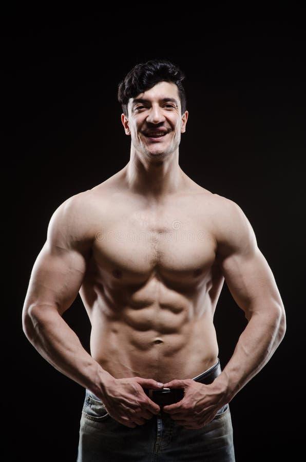 Hombre muscular que presenta en estudio oscuro imagen de archivo libre de regalías