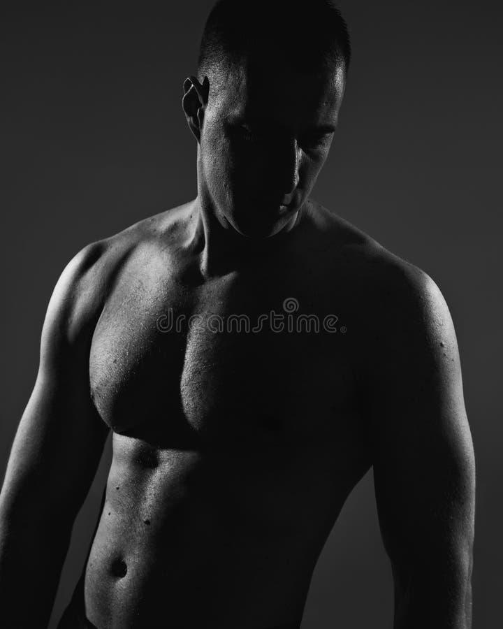 Hombre muscular que presenta en sombra foto de archivo libre de regalías