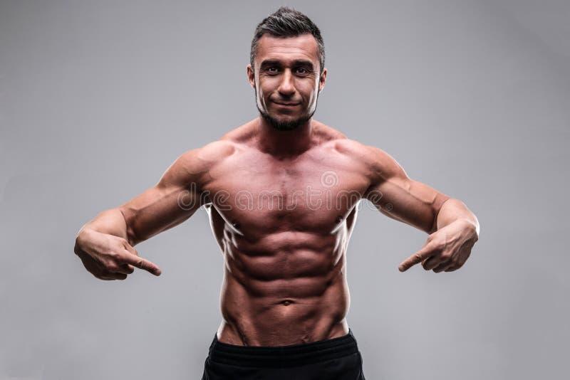 Hombre muscular que señala en su ABS imagen de archivo