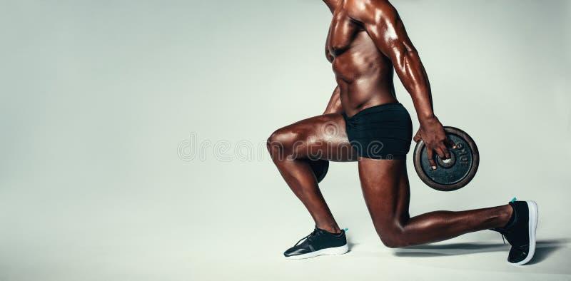 Hombre muscular que se resuelve con el peso pesado imagenes de archivo