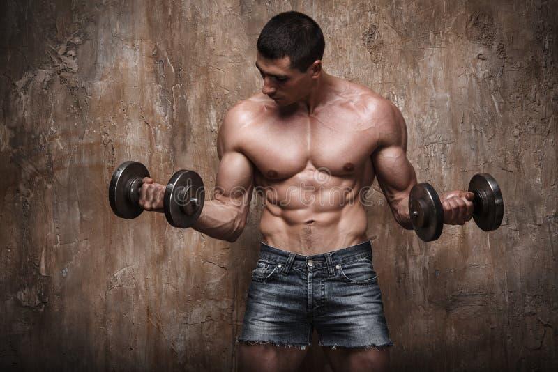 Hombre muscular que se resuelve con pesas de gimnasia en fondo de la pared foto de archivo
