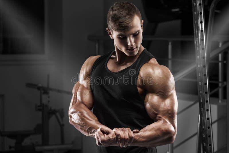 Hombre muscular que se resuelve en gimnasio Varón fuerte que muestra el bíceps de los músculos imágenes de archivo libres de regalías