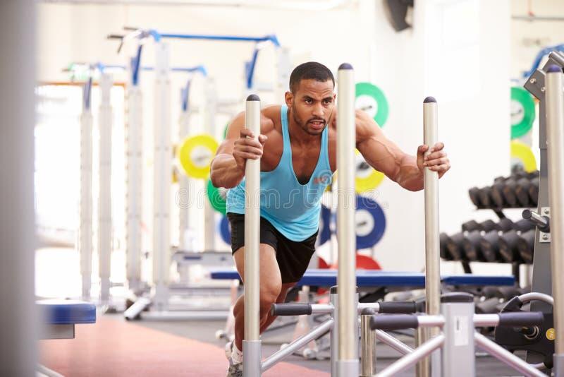 Hombre muscular que se resuelve usando el equipo en un gimnasio imagenes de archivo