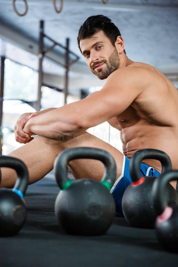 Hombre muscular que se sienta en gimnasio de la aptitud con las bolas de la caldera foto de archivo