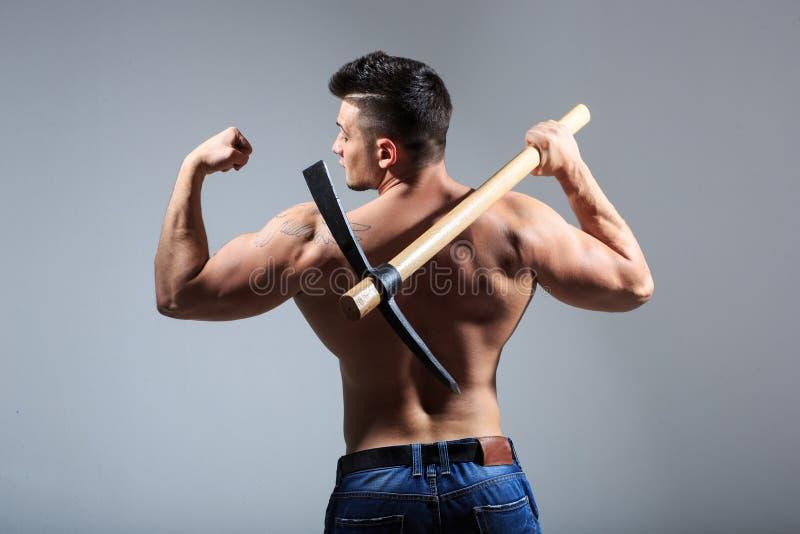 Hombre muscular que sostiene la piqueta fotografía de archivo libre de regalías