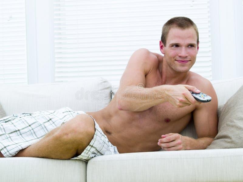 Hombre muscular que ve la TV foto de archivo libre de regalías