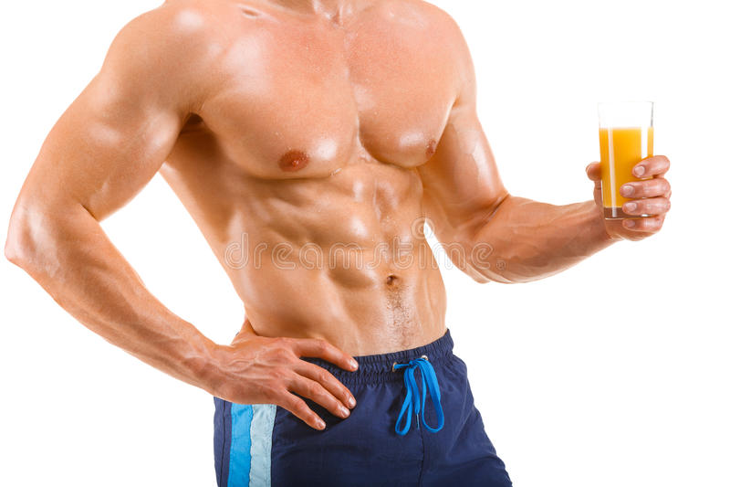 Hombre muscular sano que sostiene un vidrio con el jugo, abdominal formada, aislado imagenes de archivo