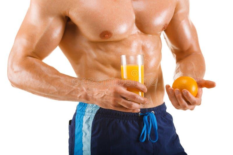 Hombre muscular sano que sostiene un vidrio con el jugo y la naranja, abdominal formada, aislados fotos de archivo