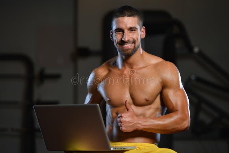 Hombre musculoso confiado en gimnasio usando el ordenador portátil foto de archivo libre de regalías