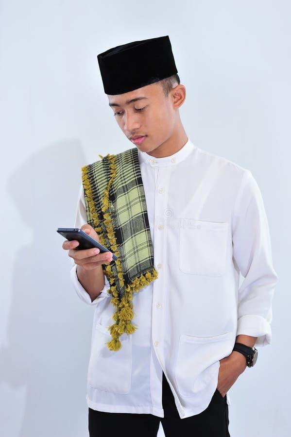Hombre musulmán asiático feliz usando un teléfono elegante fotos de archivo