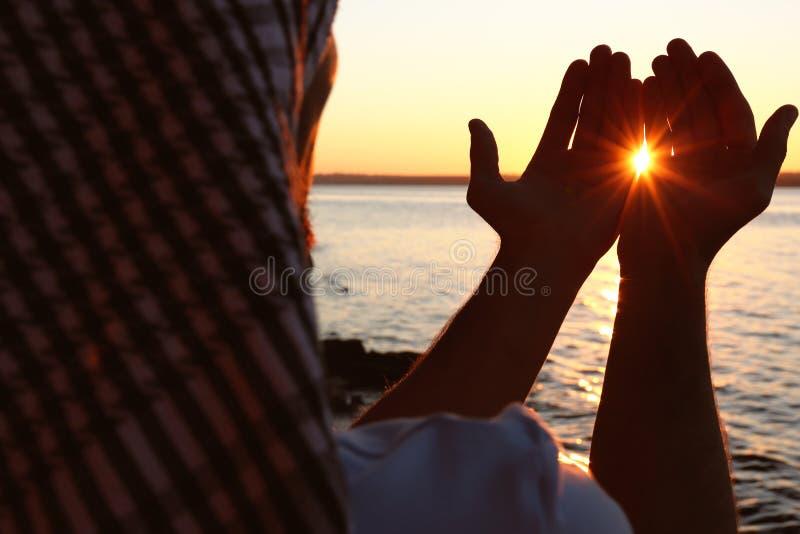 Hombre musulmán joven que ruega cerca del río en la puesta del sol fotografía de archivo