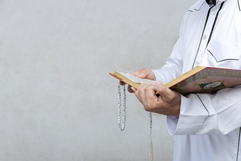 Hombre musulmán que lee un Quran imagenes de archivo