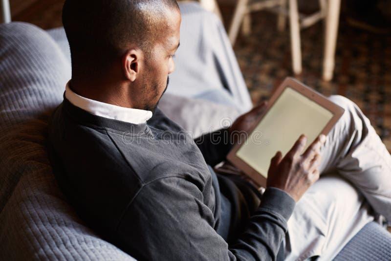 Hombre negro africano elegante usando la tableta en el sofá del sofá en la sala de estar casera fotografía de archivo libre de regalías