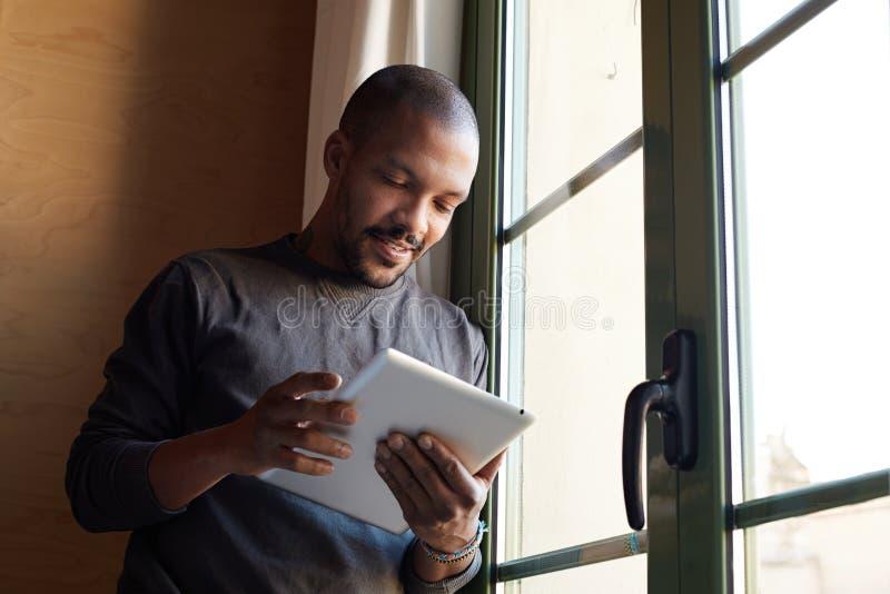 Hombre negro africano feliz usando sala de estar de la tableta en casa fotografía de archivo