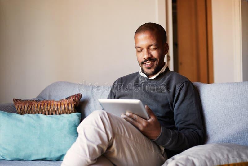 Hombre negro africano hermoso usando la tableta en el sofá del sofá en la sala de estar casera fotos de archivo libres de regalías