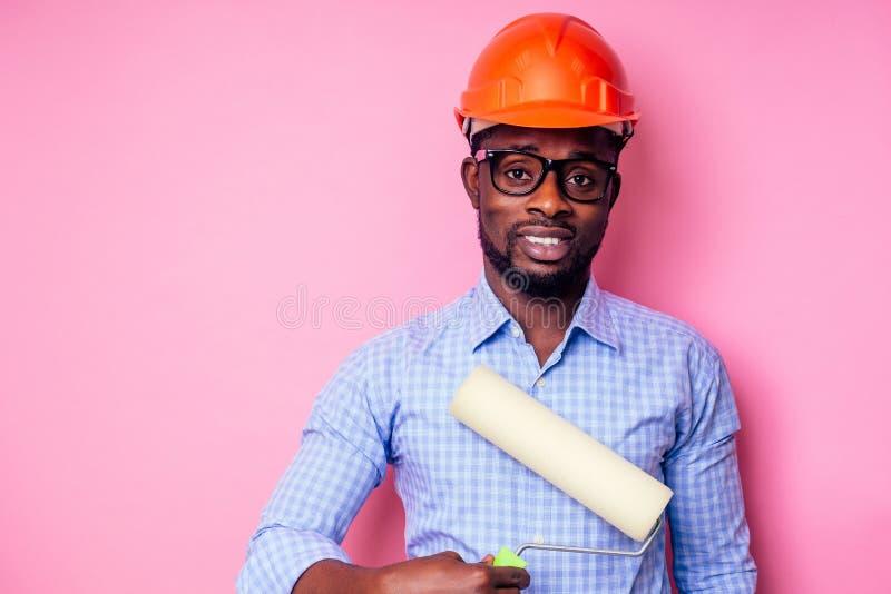 Hombre negro Africano sosteniendo rodillos de pintura en la mano pinta la pared en color rosa. pintura feliz de un constructor afr fotografía de archivo libre de regalías