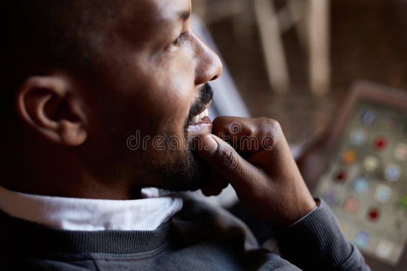 Hombre negro africano usando la tableta en el sofá del sofá en la sala de estar casera Retrato del primer foto de archivo