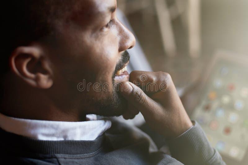 Hombre negro africano usando la tableta en el sofá del sofá en la sala de estar casera Retrato del primer flama imagenes de archivo