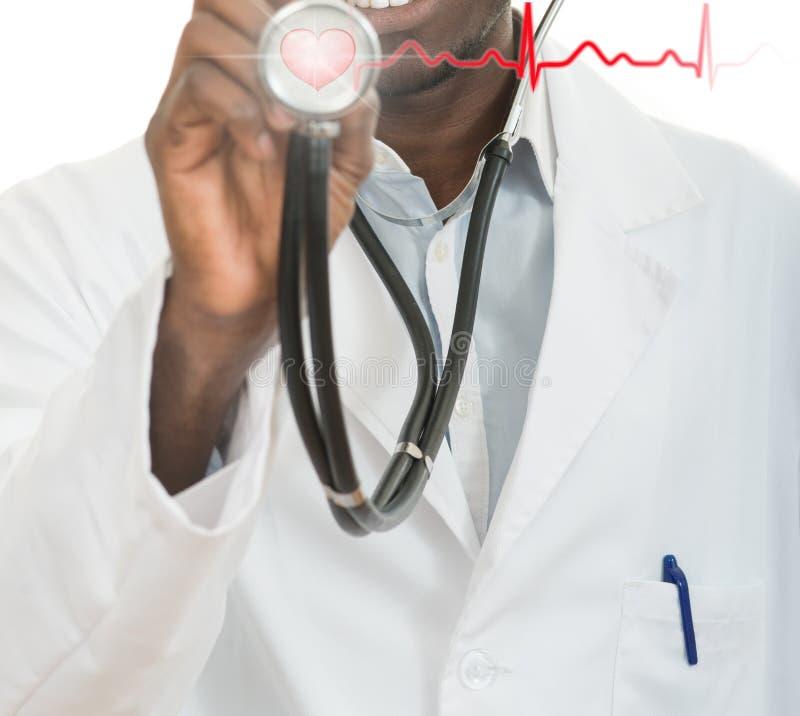 Hombre negro afroamericano del doctor con el estetoscopio con ECG del hogar foto de archivo libre de regalías