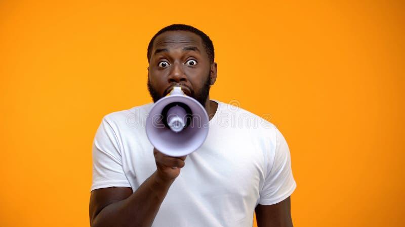 Hombre negro asustado que grita en el meg?fono, informaci?n de extensi?n, conciencia foto de archivo libre de regalías