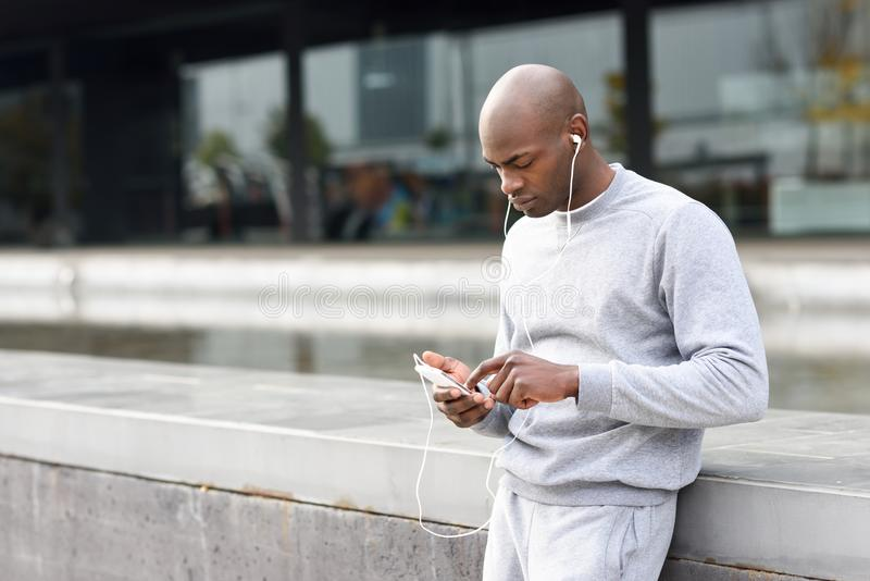 Hombre negro atractivo que escucha la música con los auriculares en urbano fotos de archivo