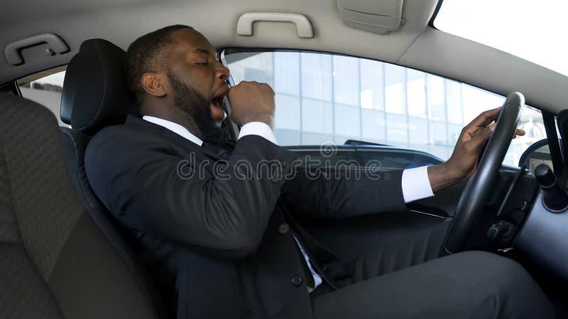 Hombre negro cansado que bosteza en coche, hombre de negocios con exceso de trabajo que conduce el coche, peligro imagenes de archivo