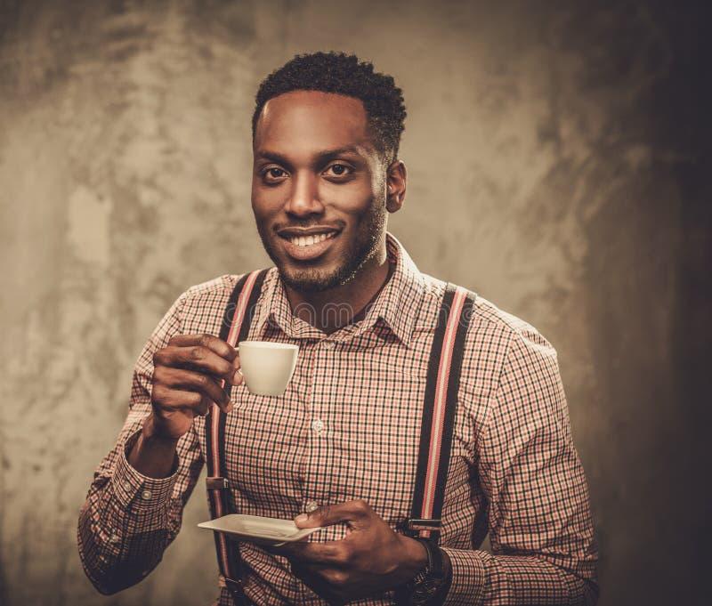 Hombre negro elegante con la taza de café que presenta en fondo oscuro imagen de archivo libre de regalías