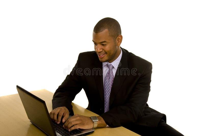 Hombre negro en el juego que trabaja en la computadora portátil imagen de archivo