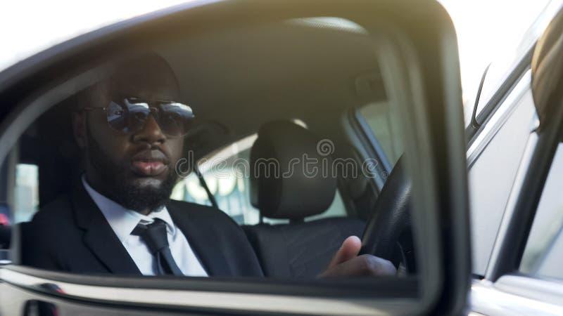 Hombre negro en las gafas de sol que conducen el coche, mirando en espejo de la lado-vista, escolta imagen de archivo libre de regalías