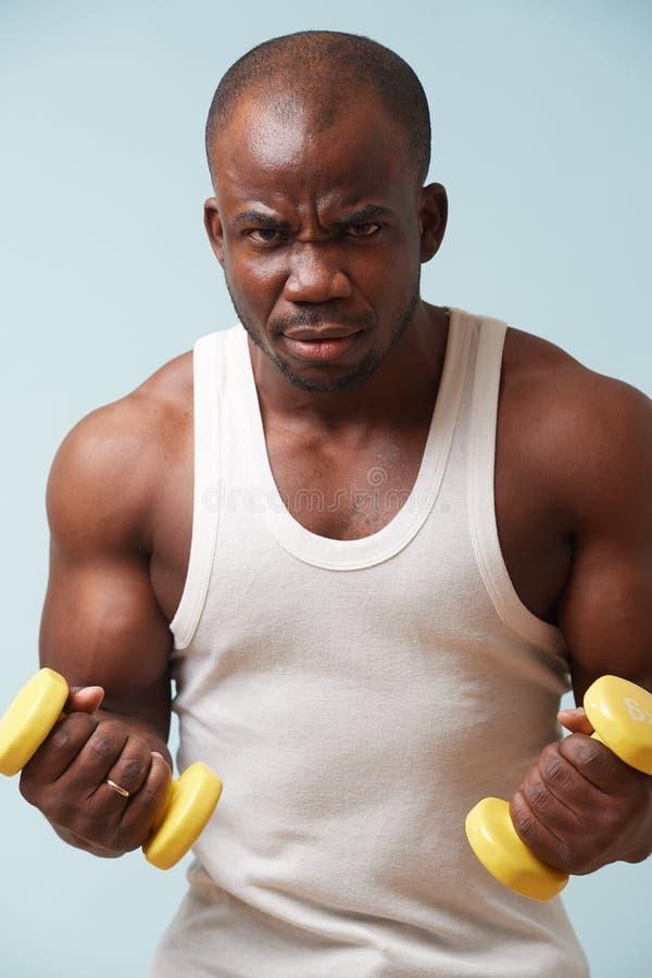 Hombre negro hermoso que hace rizos del bíceps con pesas de gimnasia ligeras Fondo azul claro fotografía de archivo libre de regalías