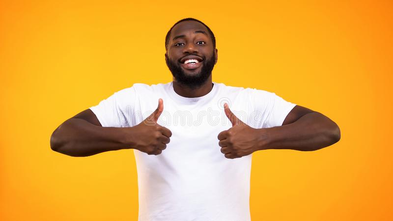 Hombre negro hermoso que sonr?e con confianza, mostrando los pulgares para arriba en fondo amarillo foto de archivo