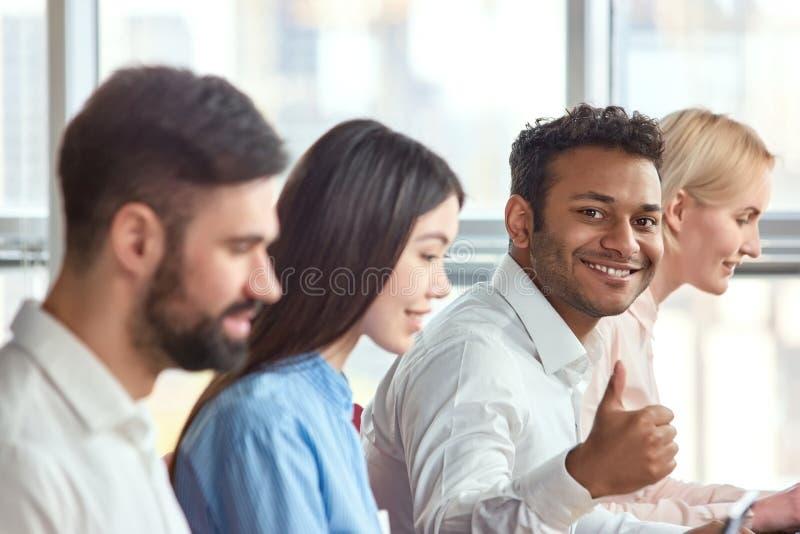 Hombre negro indio joven que se sienta que muestra el pulgar para arriba fotografía de archivo libre de regalías