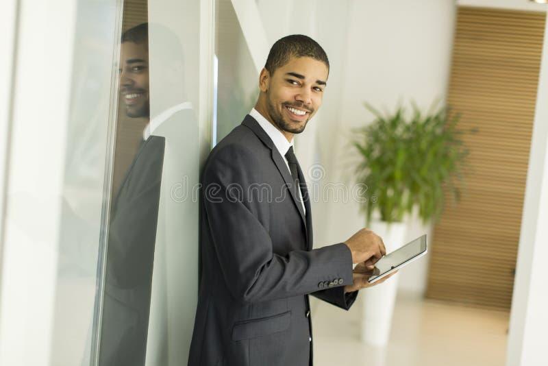 Hombre negro joven con la tableta en la oficina imagen de archivo libre de regalías