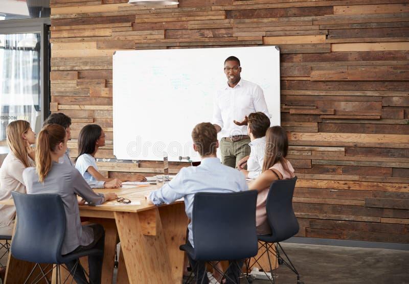 Hombre negro joven en el whiteboard que da una presentación del negocio fotografía de archivo