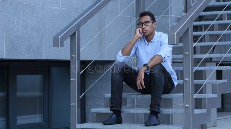 Hombre negro joven que se sienta en las escaleras y que habla en el teléfono imagen de archivo