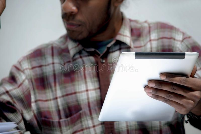 Hombre negro joven que trabaja y que estudia sosteniendo el ordenador portátil y la pluma de la tableta que hacen la preparación fotografía de archivo