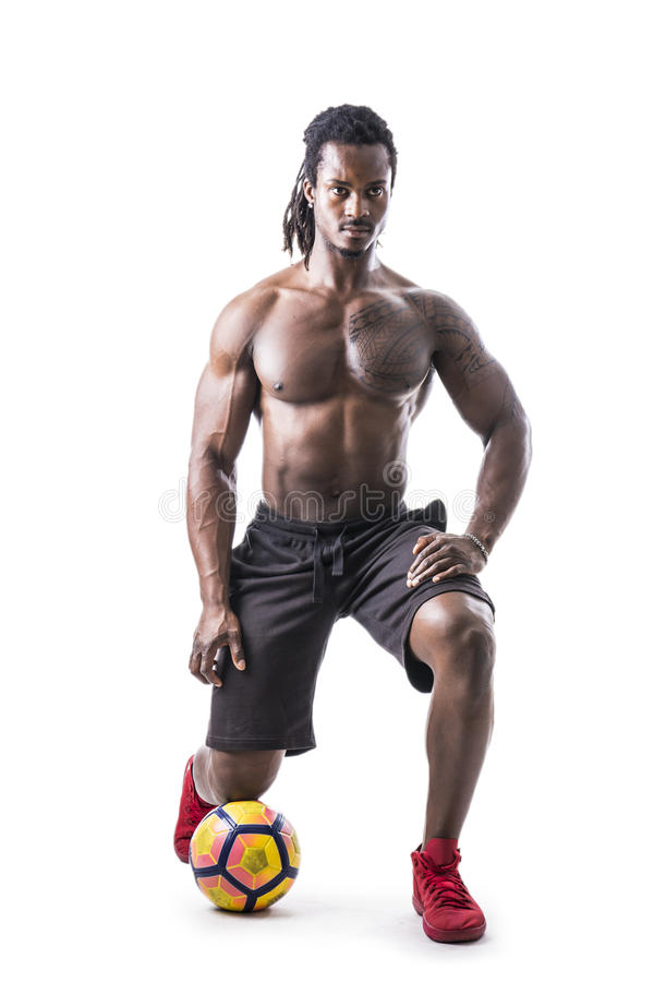 Hombre negro muscular que ejercita con el balón de fútbol fotografía de archivo