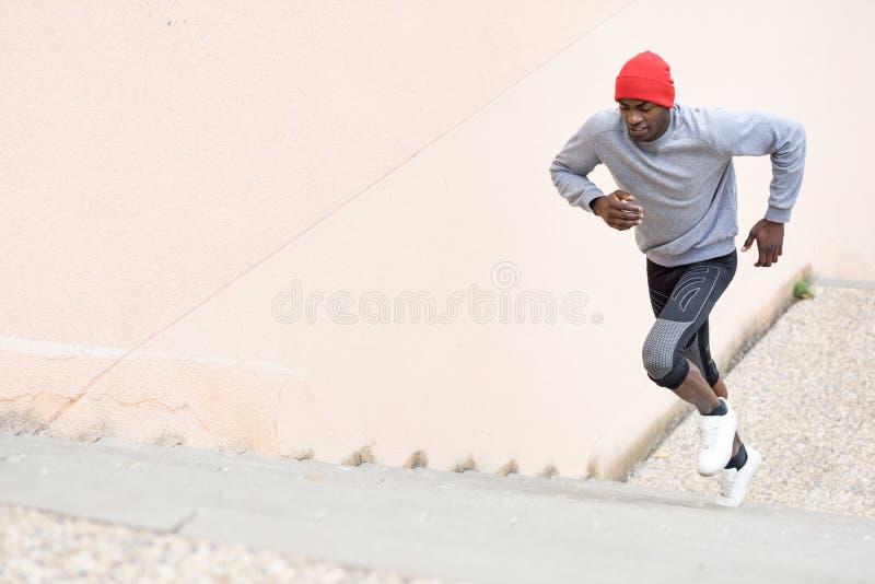 Hombre negro que corre arriba al aire libre en fondo urbano imagen de archivo