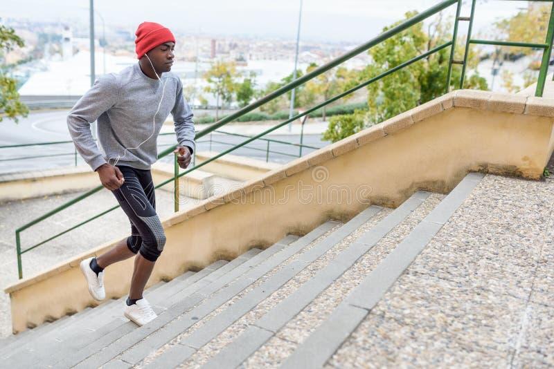 Hombre negro que corre arriba al aire libre en fondo urbano imagen de archivo libre de regalías