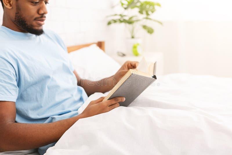 Hombre negro que estudia la literatura del negocio en cama fotografía de archivo