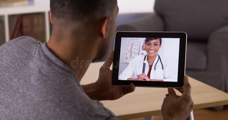 Hombre negro que habla con el doctor en la tableta fotos de archivo