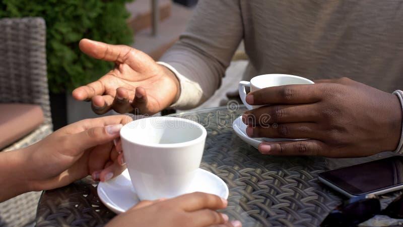 Hombre negro que habla con la mujer que se sienta en el café, colegas que beben el café junto fotos de archivo libres de regalías