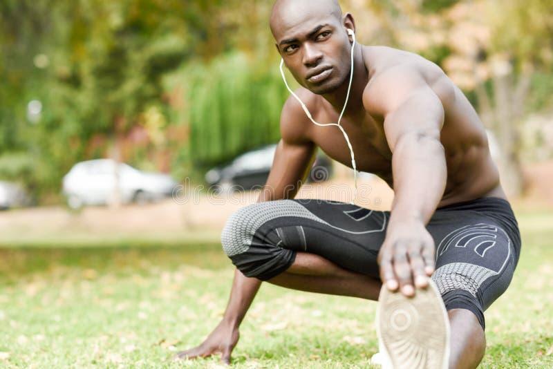 Hombre negro que hace estirar antes de correr en fondo urbano imagen de archivo libre de regalías