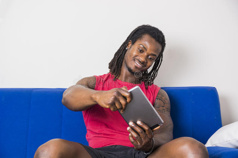 Hombre negro que juega el videojuego en la tableta imagen de archivo libre de regalías