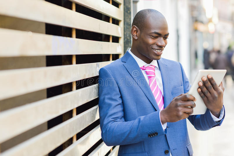 Hombre negro que mira su tableta imagen de archivo