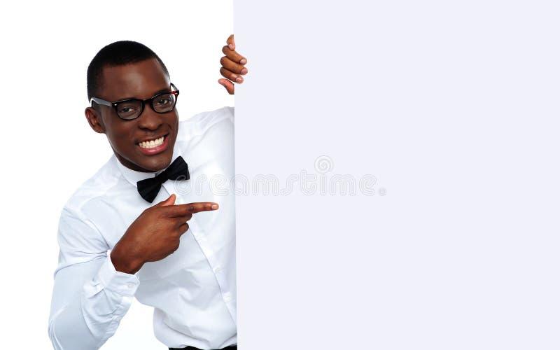Hombre negro que señala en el cartel en blanco foto de archivo libre de regalías