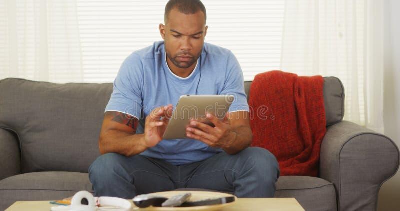 Hombre negro que se sienta en el sofá usando la tableta foto de archivo libre de regalías
