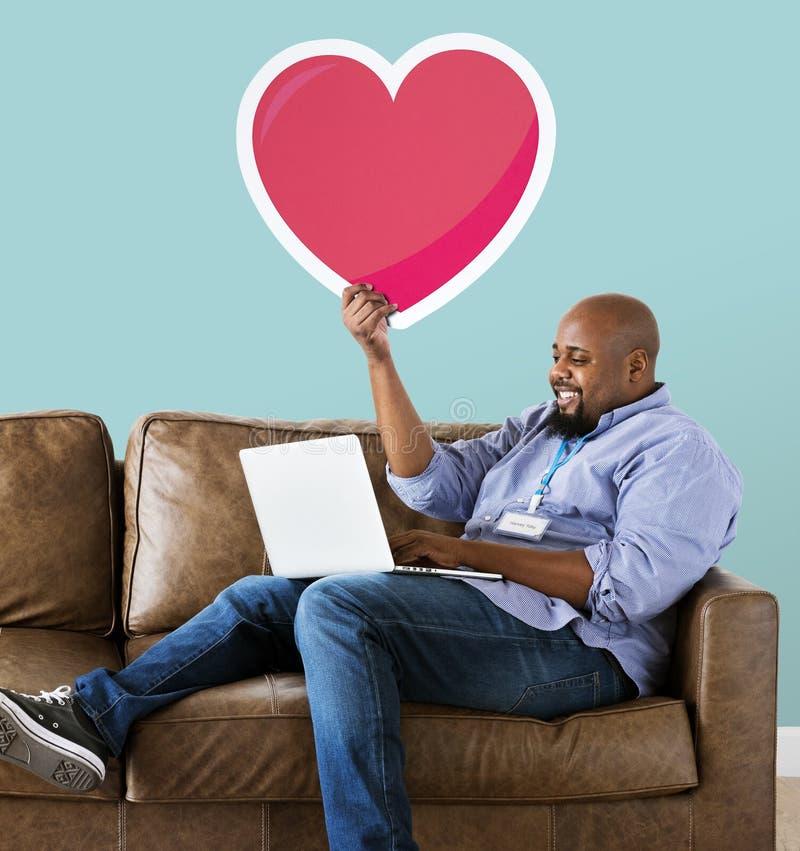 Hombre negro que se sienta en el sofá y que trabaja en el ordenador portátil fotografía de archivo libre de regalías